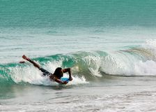 Asian man surfer laying on surfboard in wave. Asian man surfer lay on surfboard on beautiful ocean wave. Catch and riding the waves Royalty Free Stock Image