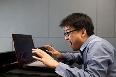 Asian man surprised with laptop computer Royalty Free Stock Image