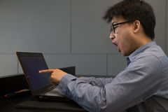Asian man surprised with laptop computer Royalty Free Stock Images