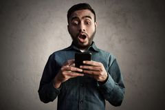 Asian men surprised looking mobile phone. Asian man surprised looking mobile phone Royalty Free Stock Image