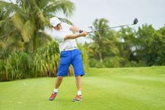 Asian man swinging club for tee-off in course. Asian golfer swinging club for tee-off in course in summer stock photos