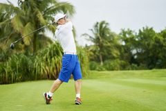 Asian man swinging club for tee-off in course. Asian golfer swinging club for tee-off in course in summer stock image