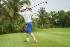 Asian man swinging club for tee-off in course. Asian golfer swinging club for tee-off in course in summer royalty free stock photos