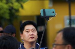 Asian man takes selfie with using a stick in the crowd. Asian man takes a selfie with using blue covered smartphone in the crowd Royalty Free Stock Photography