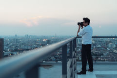 Asian man taking cityscape photo on building rooftop in low light situation. Photography, office people, or hobby concept stock image