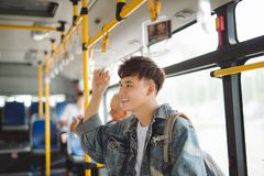 Asian man taking public transport, standing inside bus. Royalty Free Stock Images