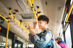Asian man taking public transport, standing inside bus. Stock Images