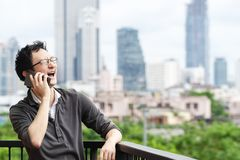 Asian man talking on smartphone smiling laughing out loud relaxing at balcony with city view copy space background. royalty free stock images