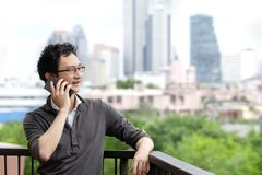 Asian man talking on smartphone smiling and standing relax at balcony with city view copy space background. stock image