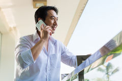 Asian man telephoning on balcony with mobile phone. Asian man telephoning on home balcony with smartphone Royalty Free Stock Photo