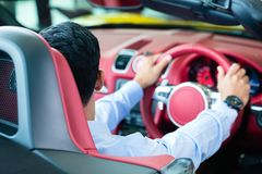 Asian man testing new sports car Royalty Free Stock Image