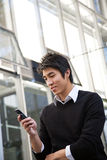 Asian man texting. A casual asian man texting on his cellphone Royalty Free Stock Images