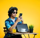 Asian Man Texting While Working on Summer Vacation Season Agains. T Yellow Background Royalty Free Stock Images