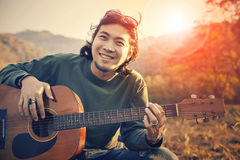 Asian man toothy smiling face with happiness playing guitar and Royalty Free Stock Image