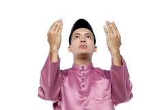 Asian man with traditional clothing rising hand for pray over white background. Portrait of young and handsome asian man with traditional clothing rising hand royalty free stock photo