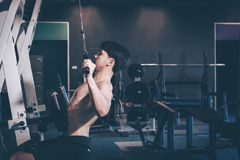 Asian man training at gym and doing pull-ups. Royalty Free Stock Photos
