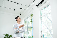 Asian man is turning air condition by remote control and smiling Royalty Free Stock Image