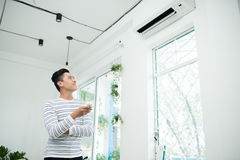 Asian man is turning air condition by remote control and smiling.  stock images