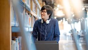 Asian man university student in college library. Young Asian man university student pushing book cart in college library finding textbook for education research stock photography