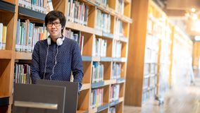 Asian man university student in college library. Young Asian man university student pushing book cart in college library finding textbook for education research royalty free stock images