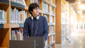 Asian man university student in college library. Young Asian man university student pushing book cart in college library finding textbook for education research stock photos