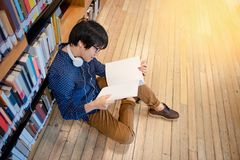 Asian man university student reading book in library. Young Asian man university student with glasses and headphones reading book sitting by bookshelf in public Stock Photos