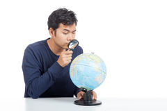 Asian man use magnifying glass searching on a world globe Royalty Free Stock Photography