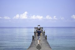 Asian man used wooden crutches walks on bridge pier boat in the sea and the bright sky at Koh Kood, Trat in Thailand stock photos