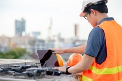 Asian man using drone and laptop for construction site survey. Young Asian man working with drone laptop and smartphone at construction site. Using unmanned stock images