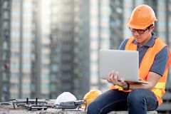 Asian man using drone and laptop for construction site survey. Young Asian man working with drone laptop and smartphone at construction site. Using unmanned royalty free stock photo