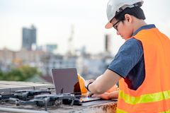 Asian man using drone and laptop for construction site survey. Young Asian man working with drone laptop and smartphone at construction site. Using unmanned royalty free stock photography