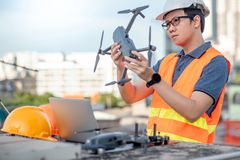 Asian man using drone and laptop for construction site survey. Young Asian man working with drone laptop and smartphone at construction site. Using unmanned royalty free stock images