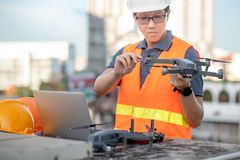 Asian man using drone and laptop for construction site survey. Young Asian man working with drone laptop and smartphone at construction site. Using unmanned royalty free stock photos