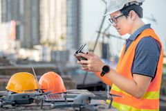 Asian man using drone and laptop for construction site survey. Young Asian man working with drone laptop and smartphone at construction site. Using unmanned stock photo