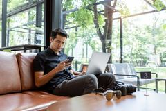 Asian man using gadgets Inspired, Confident young man working on laptop while sitting at his working place in coffee shop, stock photos