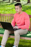Asian man using laptop in garden Stock Images