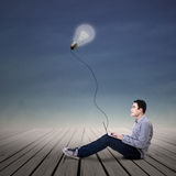 Asian man using laptop under lit bulb outdoor Stock Photo