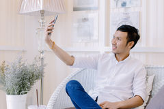 Asian man using a mobile phone  in  bakery shop Royalty Free Stock Photos