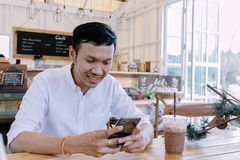 Asian man using a mobile phone and drink coffee in  bakery shop Royalty Free Stock Images