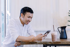 Asian man using a mobile phone and drink coffee in  bakery shop Royalty Free Stock Photo