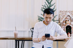 Asian man using a mobile phone and drink coffee in  bakery shop Stock Photo