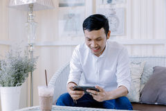 Asian man using a mobile phone and drink coffee in  bakery shop Stock Image