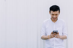 Asian man using a mobile phone smile with white walls Royalty Free Stock Image