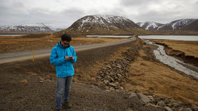 Asian man using smart phone for internet gps for road trip and s Stock Image