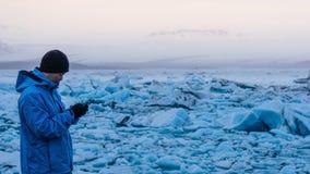 Asian man using smart phone at jokulsarlon, Glacier lagoon Iceland. World travel destination royalty free stock photo
