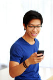 Asian man using smartphone at home Stock Photos