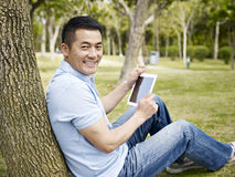 Asian Man Using Tablet Outdoors Stock Photography