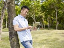 Asian man using tablet outdoors Stock Photos