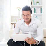 Asian man using tablet pc. Handsome Asian man using tablet computer. Smiling Southeast Asian college student relaxing and listening to music at home. Asian model Stock Photo