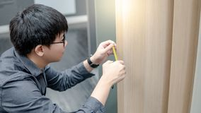Asian man using tape measure on cabinet materials. Asian man using tape measure on cabinet panel choosing materials or countertops for built-in furniture design stock photography